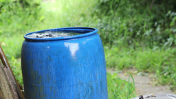 Rain water fills blue water barrel during a rain Stock Video Footage