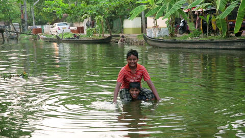 ALLEPPEY, INDIA - MARCH 2013: Two boys splashing i Stock Video Footage