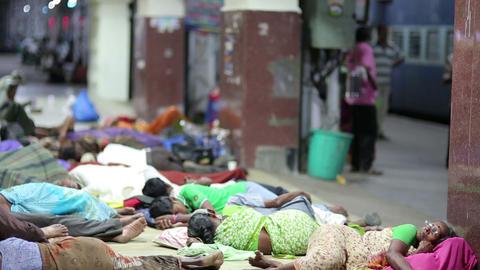 MADURAI, INDIA - MARCH 2013: People sleeping on ra Stock Video Footage