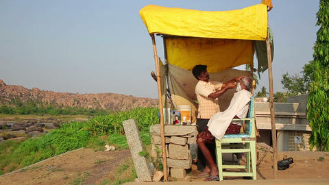 HAMPI, INDIA - APRIL 2013: Local barber at work Stock Video Footage