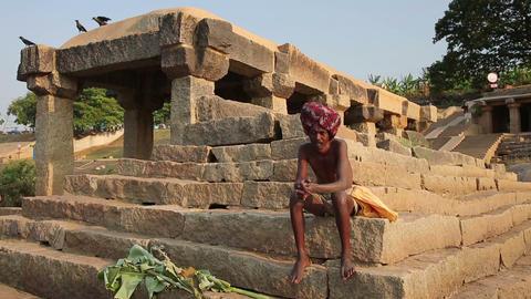 HAMPI, INDIA - APRIL 2013: Man sitting on stone st Stock Video Footage