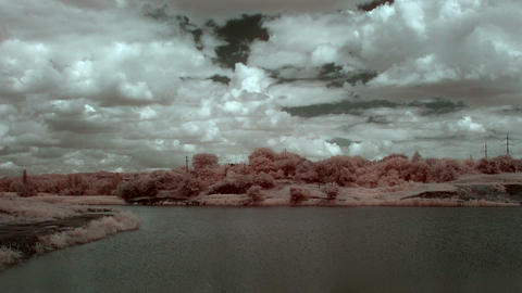 InfraRed landscape: Movement of clouds over the re Stock Video Footage
