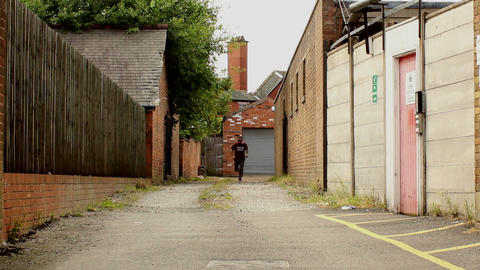 Guy runs narrow alley toward camera Stock Video Footage