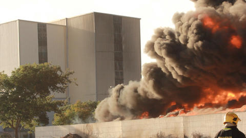 firefighters battle blaze in packaging factory Stock Video Footage