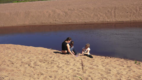 Mom and daughters on the sandy Bank of the river.  Footage