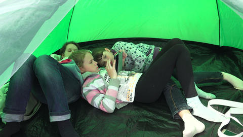 Mom and daughters having a rest in a tent. 4K Footage