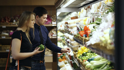 Young couple choosing fresh vegetables in supermar Footage