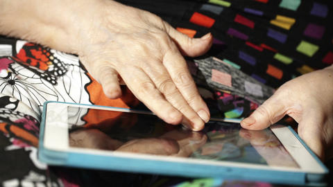 Elderly woman scrolling slowly photos on touchpad Live Action
