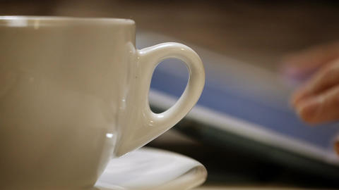 Having a cup of coffee during working with pad Stock Video Footage