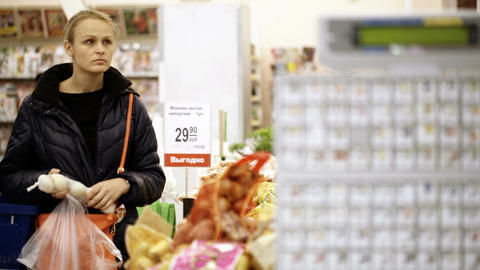 Young woman shopping in supermarket and choosing v Footage
