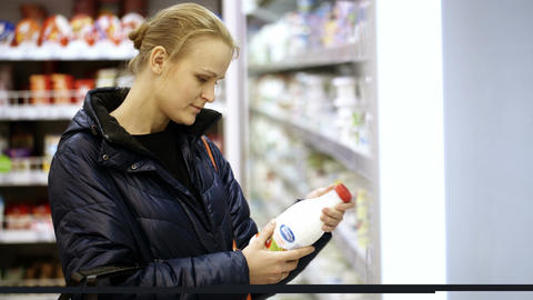 Woman putting a bottle of milk in her shopping bas Footage