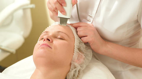 Woman getting ultrasonic face cleaning at beauty s Footage