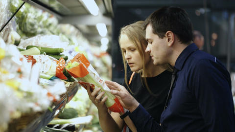 Man and woman buying fresh vegetables in grocery Stock Video Footage