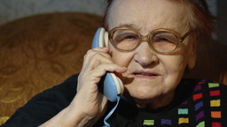 Elderly woman in glasses taking a call Footage