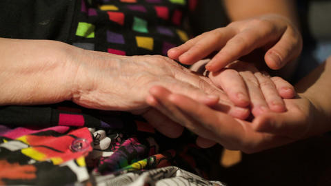 Young woman stroking her grandmothers hands Stock Video Footage