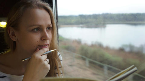 Young woman making notes while traveling by train Footage