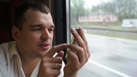 Young man typing sms in moving train Stock Video Footage