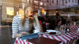 Woman in cafe using tablet pc and eating dessert Footage