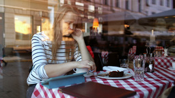 Woman in cafe using tablet pc and eating dessert Stock Video Footage