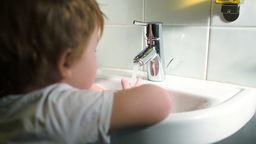 Boy washing hands with soft soap and turning off w Footage