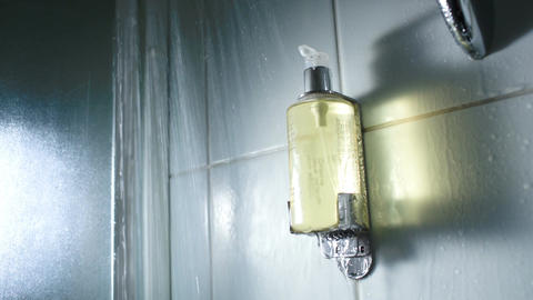 Hands pushing a container with soap under shower s Stock Video Footage