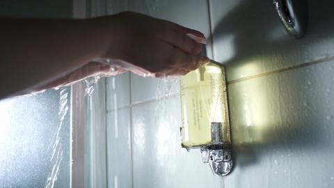 Hands pushing a container with soap under shower s Footage