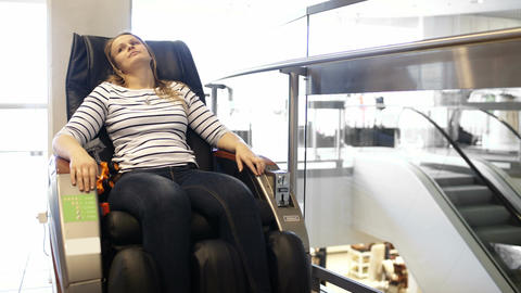 Woman having a rest in massage chair in the shoppi Footage