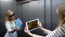 Young woman with pad in the lift posing and taking Footage