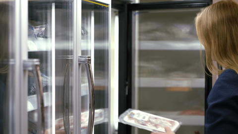Woman taking frozen product from the fridge in the Footage