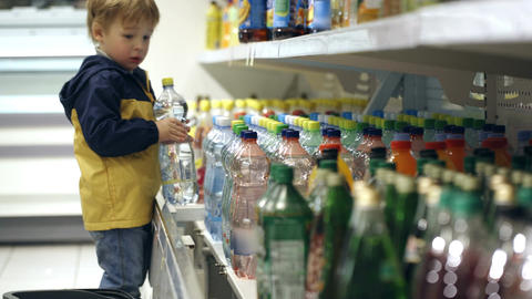 Little boy in the shop putting mineral water into  Footage