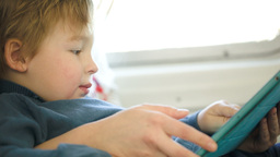Boy in the train using touchpad held by mother Footage