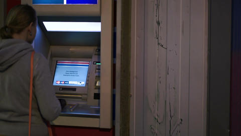 Woman inserting bank card into atm to get cash Live Action