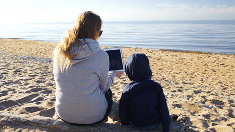 Mother and son on the beach with tablet pc Stock Video Footage
