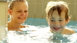 Happy boy and his mother swimming in the pool Stock Video Footage