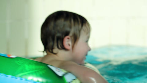 Back view of a kid swimming in rubber ring in the  Footage