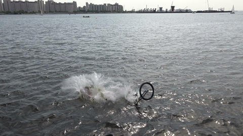Jump on the bike into the water. 4K Footage