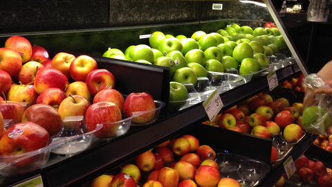 Woman selecting fresh green apples in grocery stor Footage