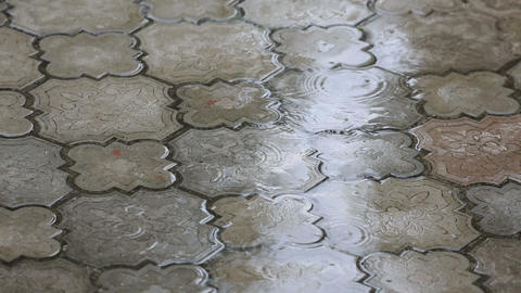 Rain water drops falling on the pavement Footage