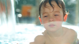 Boy in the swimming pool splashing water Footage