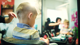 Hairdresser cutting childs hair while he playing w Footage