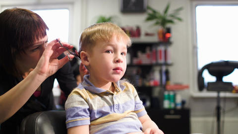 Child getting a haircut from a professional hairdr Footage