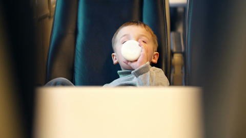 Boy in the train drinking milk from the bottle Stock Video Footage