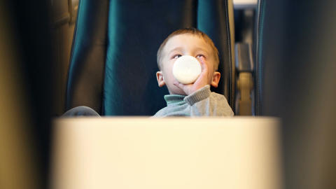 Boy in the train drinking milk from the bottle Footage