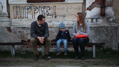 Parents and their child sitting on the bench near  Footage