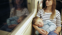 Tired woman in the train with sleeping son on her Stock Video Footage