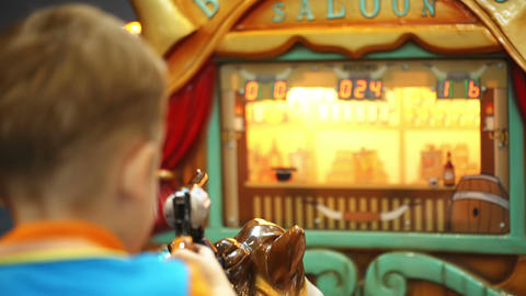 Boy riding a toy horse and shooting with toy gun Stock Video Footage