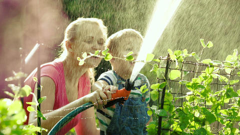 Mom and son watering the garden together Stock Video Footage