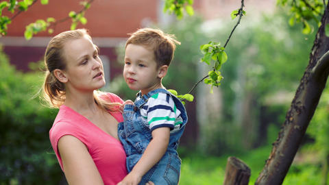 Mother holding her son and they talking outdoor Stock Video Footage