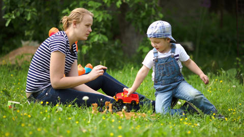 Mother and son playing outdoor on the green lawn Footage