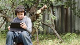 Teenager in earphones using touchpad outdoor Footage